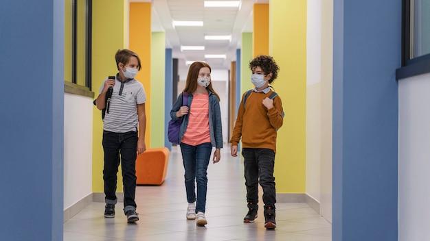 Vista frontal de três crianças no corredor da escola com máscaras médicas Foto gratuita