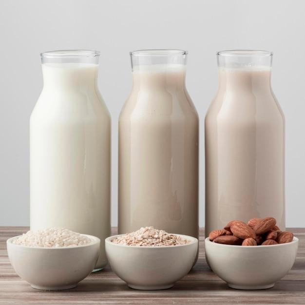 Vista frontal de três garrafas de leite diferentes Foto gratuita
