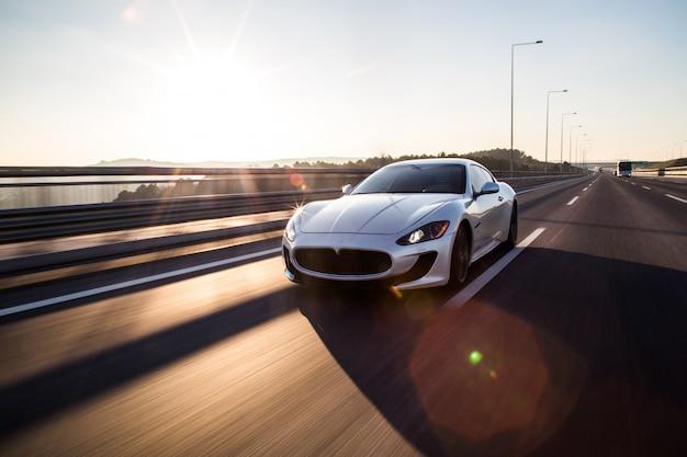 Vista frontal de um carro esporte prateado de alta velocidade, dirigindo na estrada. Foto gratuita
