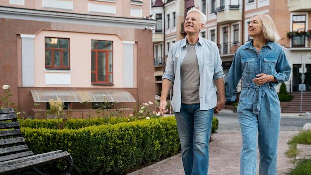 Vista frontal de um casal de idosos de mãos dadas na cidade Foto gratuita
