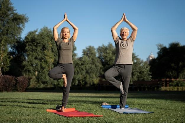 Vista frontal de um casal de idosos fazendo ioga ao ar livre Foto gratuita