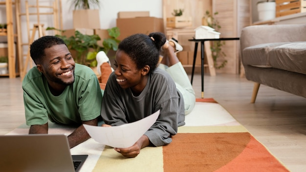 Vista frontal de um casal sorridente fazendo planos para redecorar a casa com um laptop Foto gratuita