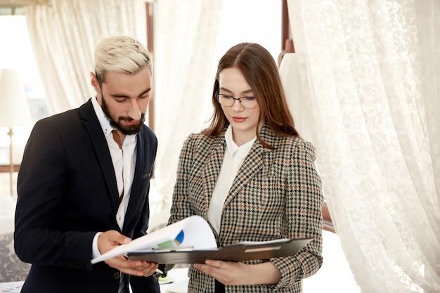 Vista frontal de um empresário bonitão e empresária atraente que estão olhando para o arquivo com documentos Foto gratuita