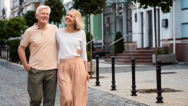 Vista frontal de um feliz casal de idosos dando um passeio pela cidade Foto gratuita