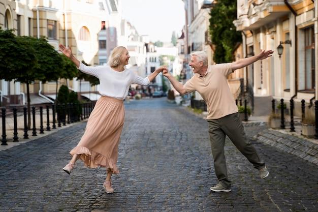 Vista frontal de um feliz casal de idosos na cidade Foto Premium