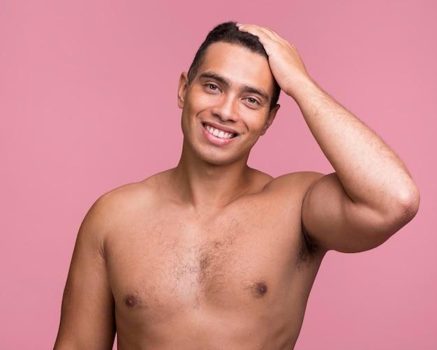 Vista frontal de um homem bonito sorridente posando sem camisa Foto gratuita