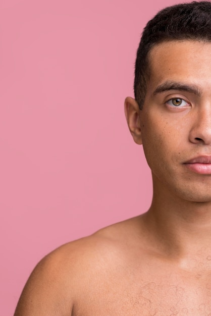 Vista frontal de um homem posando enquanto mostra metade do rosto com espaço de cópia Foto gratuita