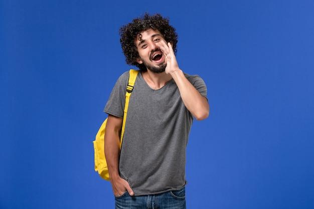 Vista frontal de um jovem do sexo masculino com camiseta cinza e mochila amarela, chamando alguém na parede azul Foto gratuita