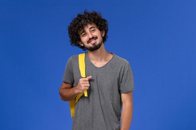 Vista frontal de um jovem homem em uma camiseta cinza usando uma mochila amarela sorrindo na parede azul Foto gratuita