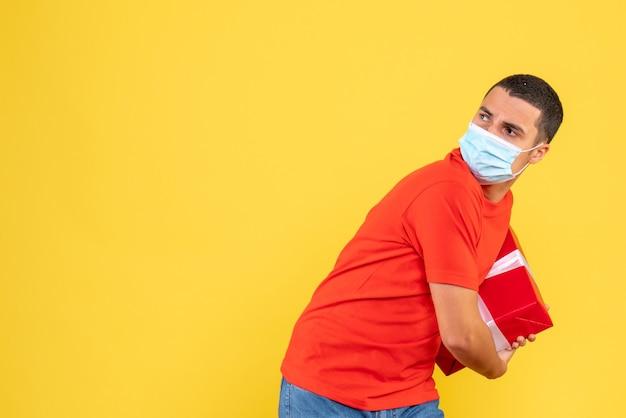 Vista frontal de um jovem segurando uma máscara estéril na parede amarela Foto gratuita