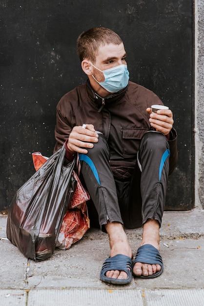 Vista frontal de um morador de rua com máscara médica ao ar livre e sacola plástica Foto Premium