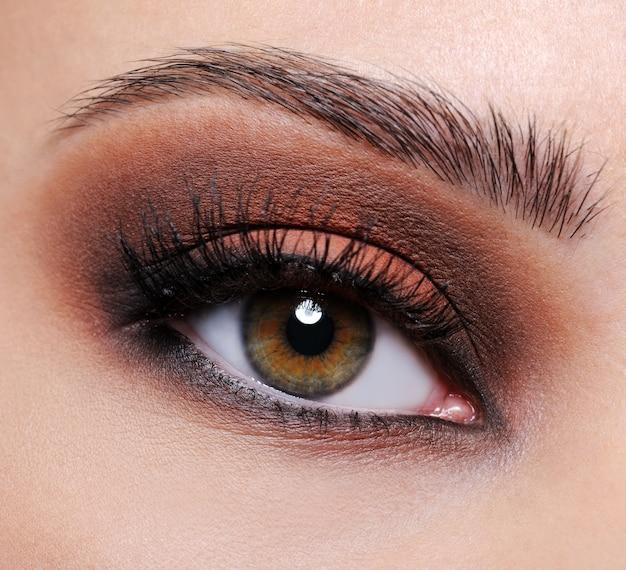 Vista frontal de um olho feminino em close-up com maquiagem de sombra marrom Foto gratuita