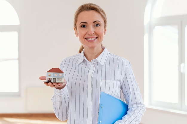 Mulher segurando miniatura de casa, com pasta na mão e roupa social para ilustrar um corretor de imóveis