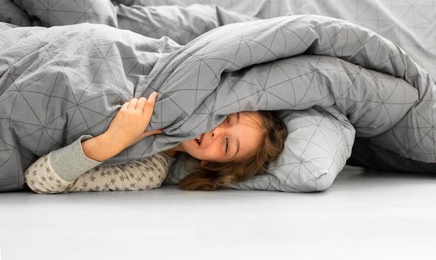 Vista frontal de uma garota sorridente na cama Foto gratuita
