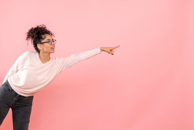 Vista frontal de uma jovem apontando na parede rosa Foto gratuita
