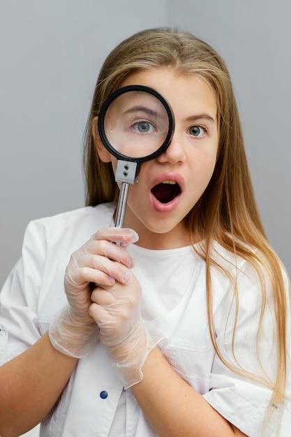 Vista frontal de uma jovem cientista curiosa usando uma lupa Foto gratuita