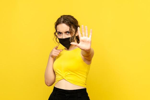 Vista frontal de uma jovem com máscara na parede amarela Foto gratuita