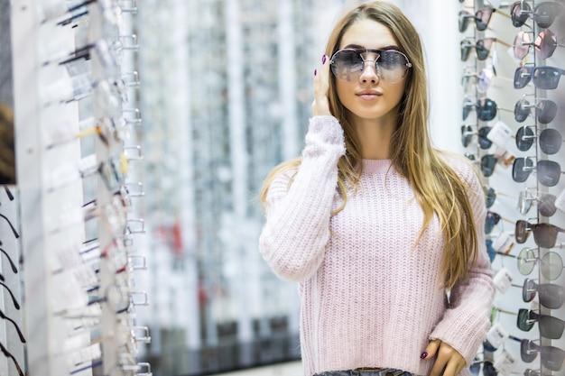 Vista frontal de uma jovem de suéter branco experimente óculos em loja profissional na Foto gratuita