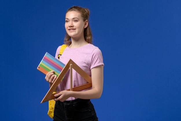 Vista frontal de uma jovem mulher com uma camiseta rosa segurando uma figura triangular de madeira e um caderno na parede azul Foto gratuita
