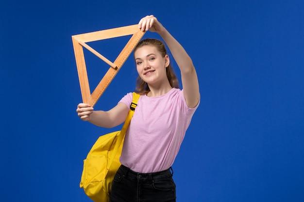 Vista frontal de uma jovem mulher com uma camiseta rosa segurando uma figura triangular de madeira sorrindo na parede azul Foto gratuita