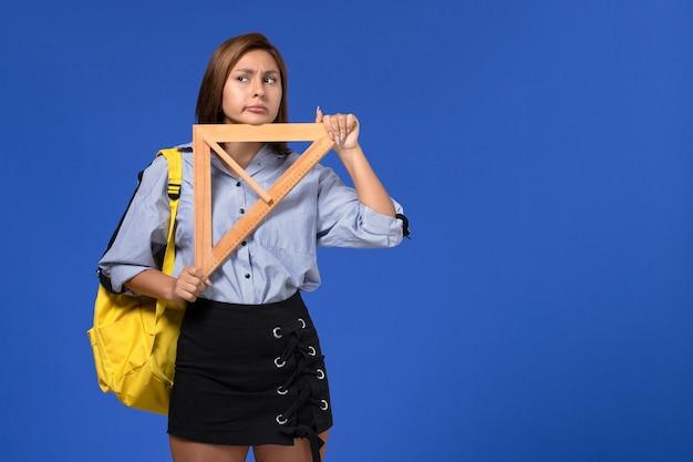 Vista frontal de uma jovem mulher de camisa azul, segurando um triângulo de madeira e pensando na parede azul Foto gratuita