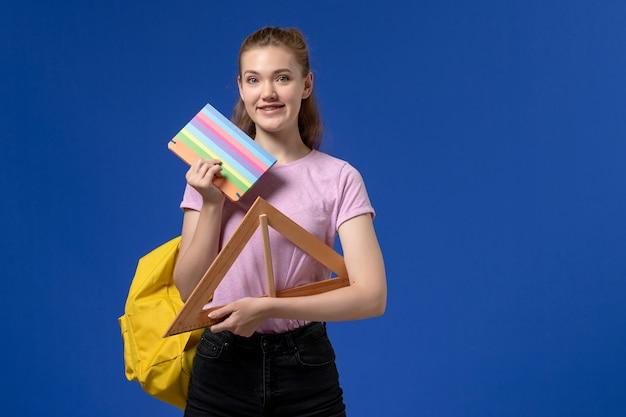 Vista frontal de uma jovem mulher em uma camiseta rosa segurando uma figura triangular de madeira e um caderno sorrindo na parede azul Foto gratuita