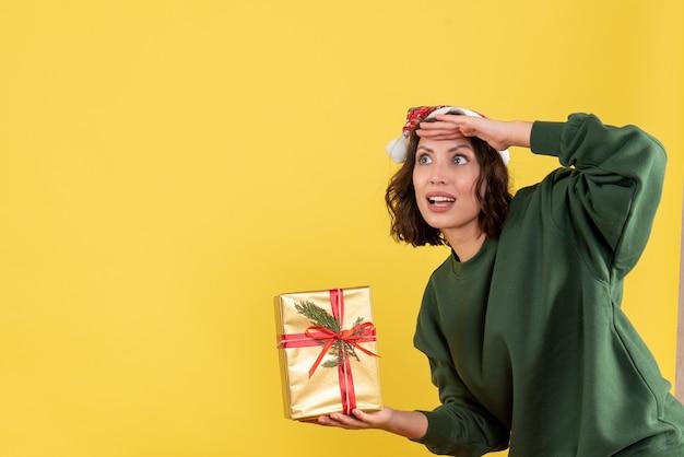 Vista frontal de uma jovem segurando um pequeno presente de natal na parede amarela Foto gratuita