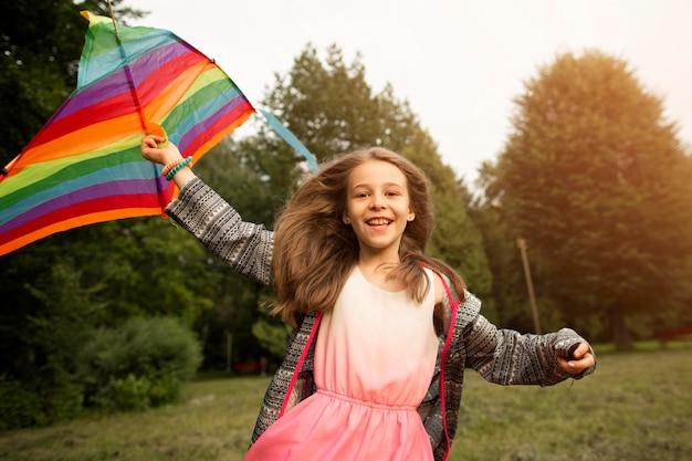 Vista frontal de uma linda garota feliz com pipa Foto gratuita