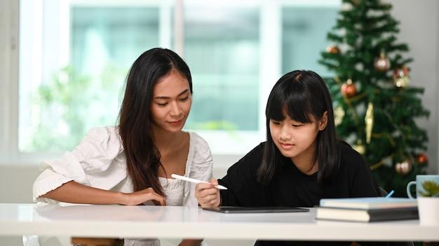 Vista frontal de uma linda mulher ajudando a filha a fazer o dever de casa online no tablet digital em casa. Foto Premium