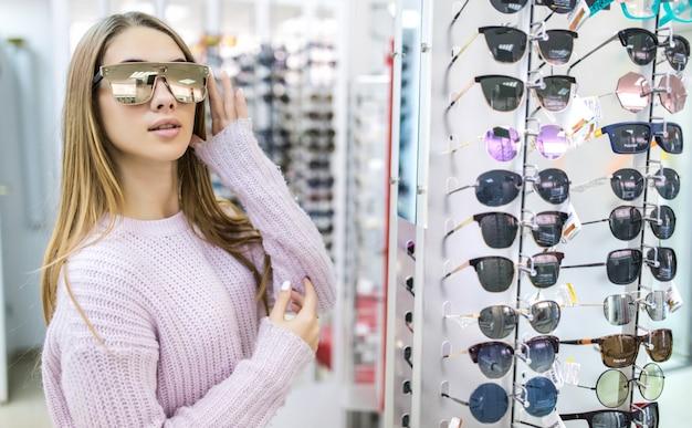 Vista frontal de uma linda mulher com suéter branco experimente óculos em loja profissional na Foto gratuita