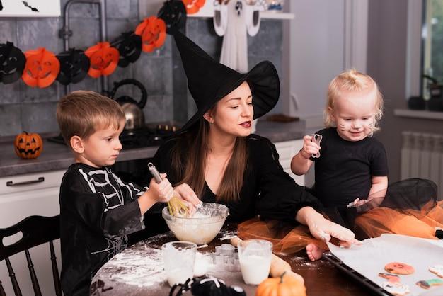 Vista frontal de uma mãe e seus filhos fazendo biscoitos de halloween Foto gratuita