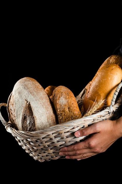 Vista frontal de uma mão segurando uma cesta de pão Foto gratuita