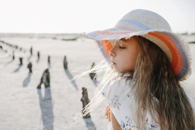 Vista frontal de uma menina com cabelos loiros, vestida de chapéu na praia com os olhos fechados Foto gratuita