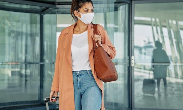 Vista frontal de uma mulher com máscara médica carregando bagagem no aeroporto durante a pandemia Foto gratuita