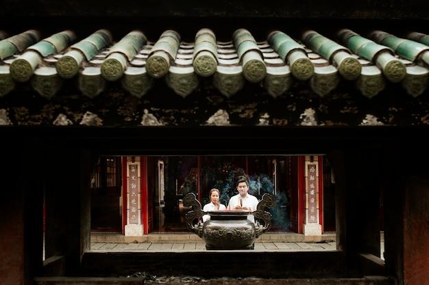 Vista frontal de uma mulher e um homem orando no templo com incenso queimando Foto gratuita
