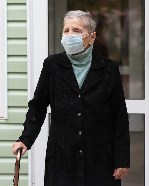 Vista frontal de uma mulher idosa com máscara médica e bengala Foto gratuita