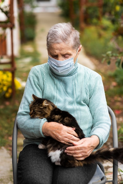 Vista frontal de uma mulher idosa com máscara médica e gato na casa de repouso Foto gratuita