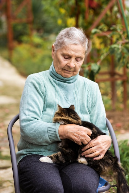 Vista frontal de uma mulher idosa com um gato na casa de repouso Foto gratuita