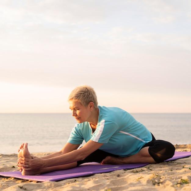Vista frontal de uma mulher madura fazendo ioga na praia Foto gratuita