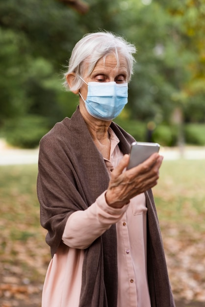 Vista frontal de uma mulher mais velha com máscara médica e smartphone Foto gratuita