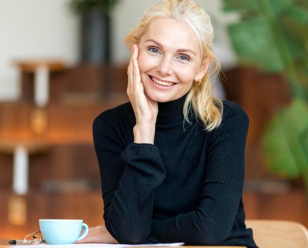 Vista frontal de uma mulher mais velha sorridente, posando enquanto toma um café Foto gratuita