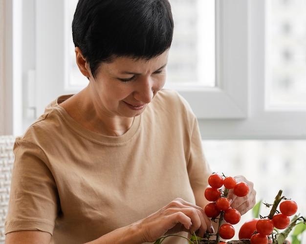 Vista frontal de uma mulher sorridente cuidando de uma planta de tomate de interior Foto Premium