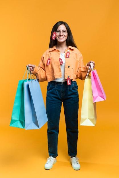 Vista frontal de uma mulher sorridente posando com sacolas de compras e etiquetas Foto gratuita