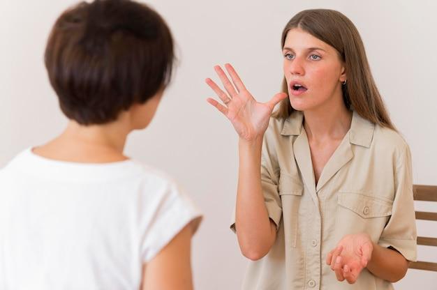 Vista frontal de uma pessoa ensinando a língua de sinais à mulher Foto Premium
