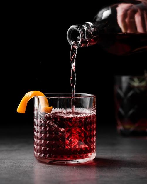 Vista frontal de vidro de enchimento de vinho Foto gratuita