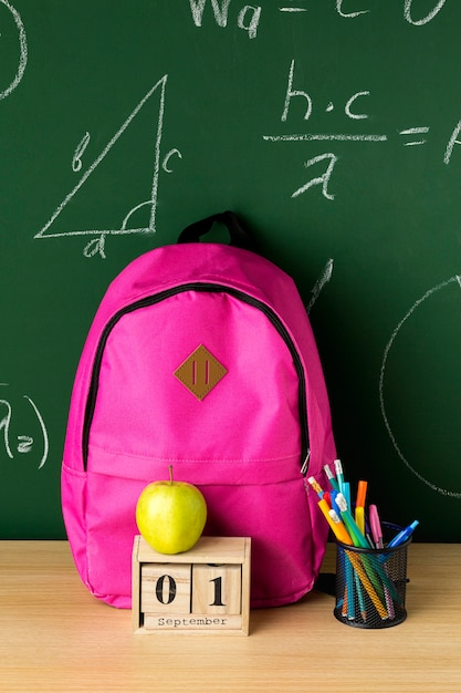 Vista frontal de volta à mochila escolar com maçã e lápis Foto gratuita