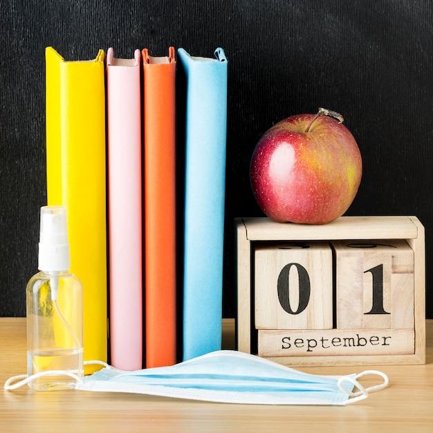 Vista frontal de volta ao essencial da escola com livros e apple Foto gratuita