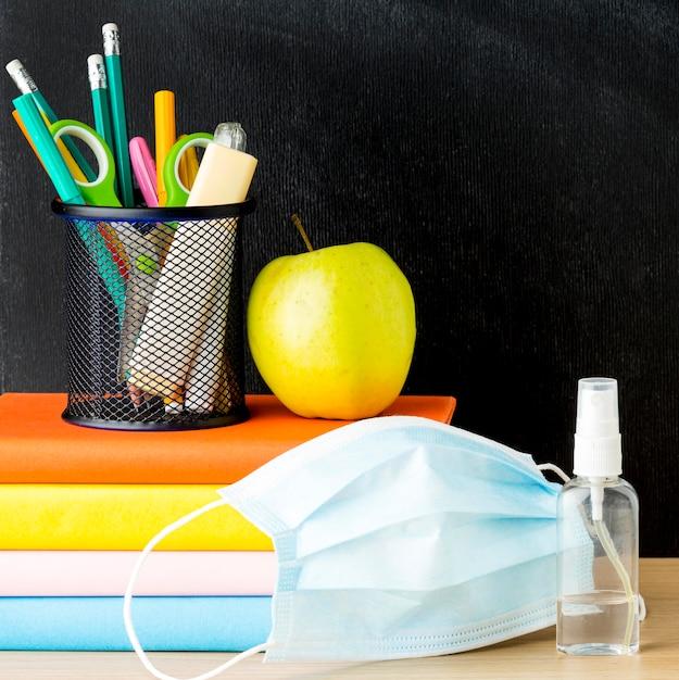 Vista frontal de volta ao material escolar com máscara médica e livros Foto Premium