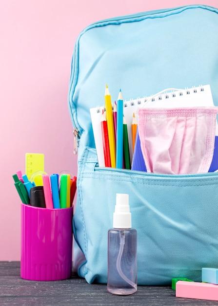 Vista frontal de volta para papelaria escolar com mochila e desinfetante para as mãos Foto gratuita