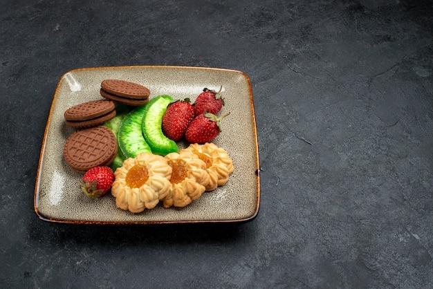 Vista frontal deliciosos biscoitos de chocolate e simples com morangos vermelhos frescos em bolo de biscoito de açúcar de parede cinza escuro Foto gratuita